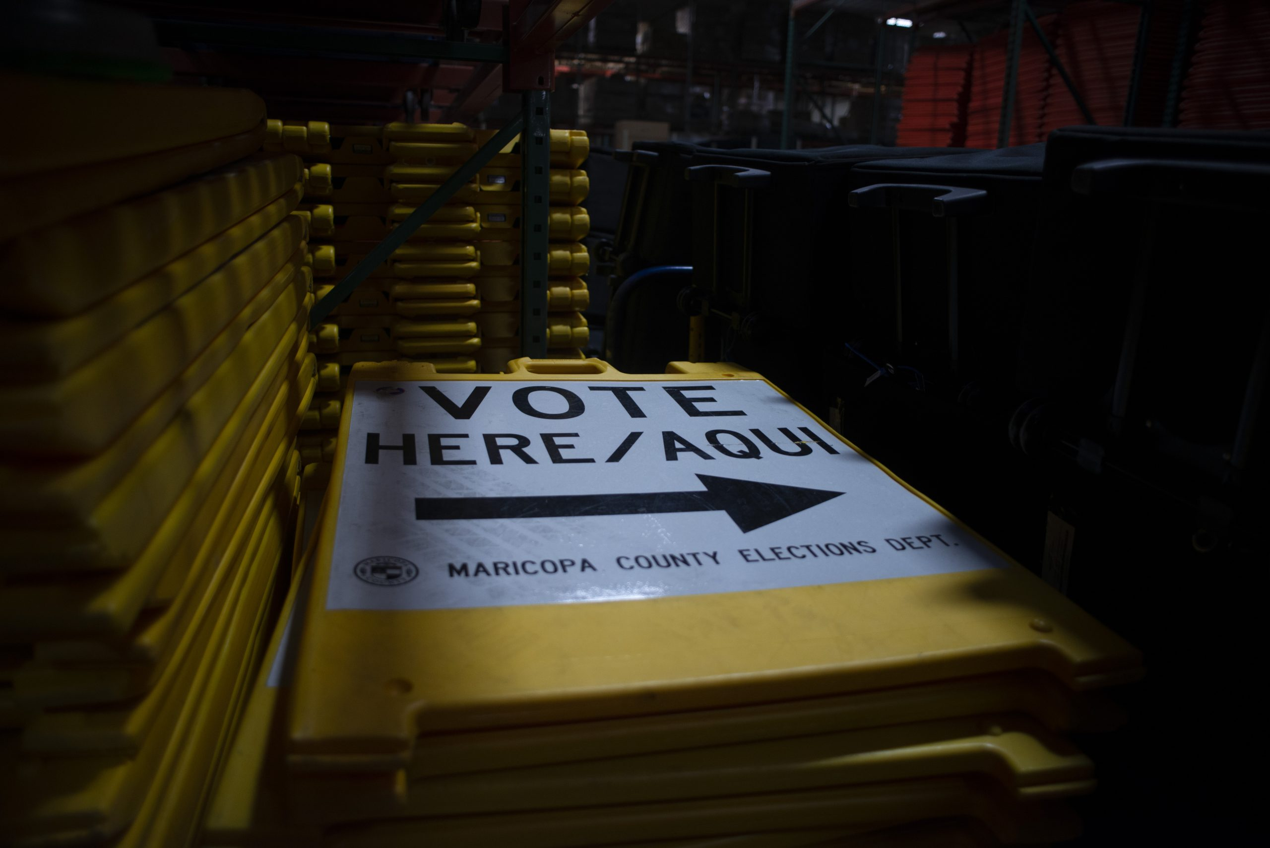 """Yellow """"Vote Here"""" signs are stacked on large metal shelving units within a warehouse at the Maricopa County Tabulation and Election Center in downtown Phoenix on Sept. 25, 2020. (Photo by Brandon Quester 