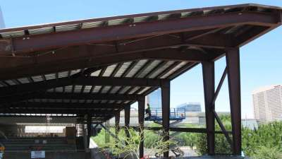 View of upper corner of shaded walkway with columns, rafters, and roof panels exposed