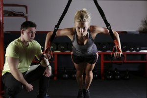 Woman On TRX with Trainer