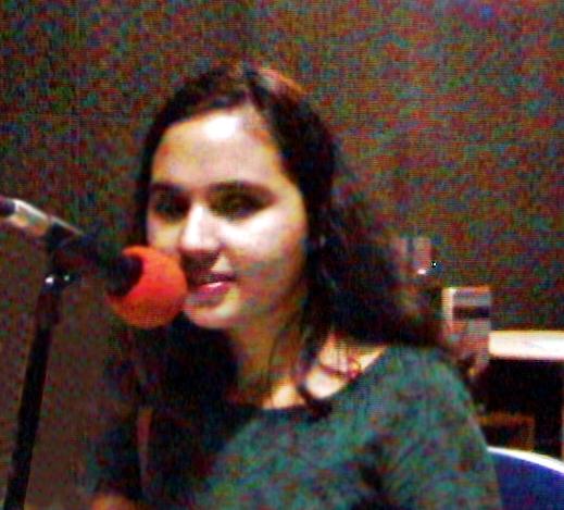 #PraCegoVer: Na foto,  Thaiane encontra-se em um estúdio de rádio e tem a frente de si um microfone vermelho, posicionado rente aos próprios lábios.  (Foto/reprodução: Lorena de Paula)