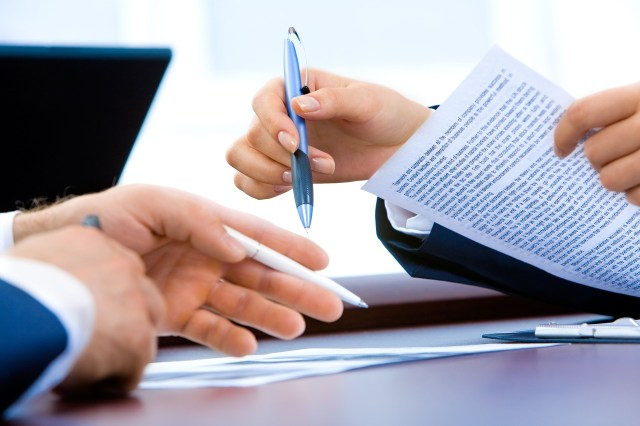 Two people reading a moving insurance contract.