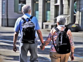 Two elderly people walking down the street