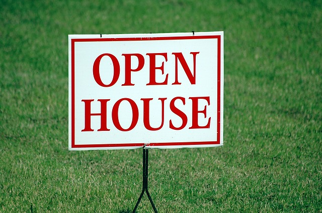 Open house sign symbolizing buying a home due to job offer in another state.