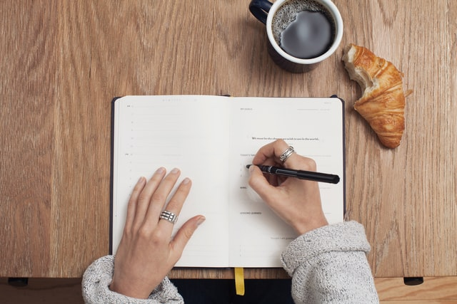 A person writing a list of 5 things to pack first when moving in a notebook next to a coffee and a croissant