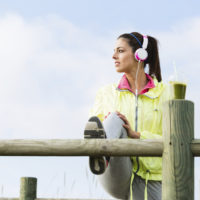 Fitness woman stretching for warming up before  fitness workout and exercising at beach on spring or summer. Fit brunette girl and detox smoothie drink.