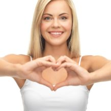 picture of woman in white tank showing heart shape with hands