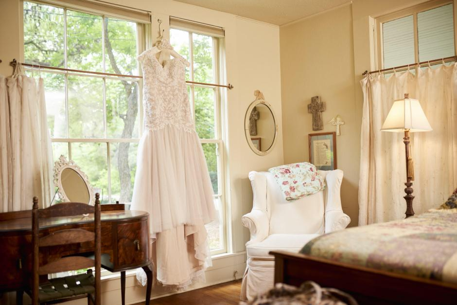 Bride's wedding dress hangs in historic Gruene Estate room.