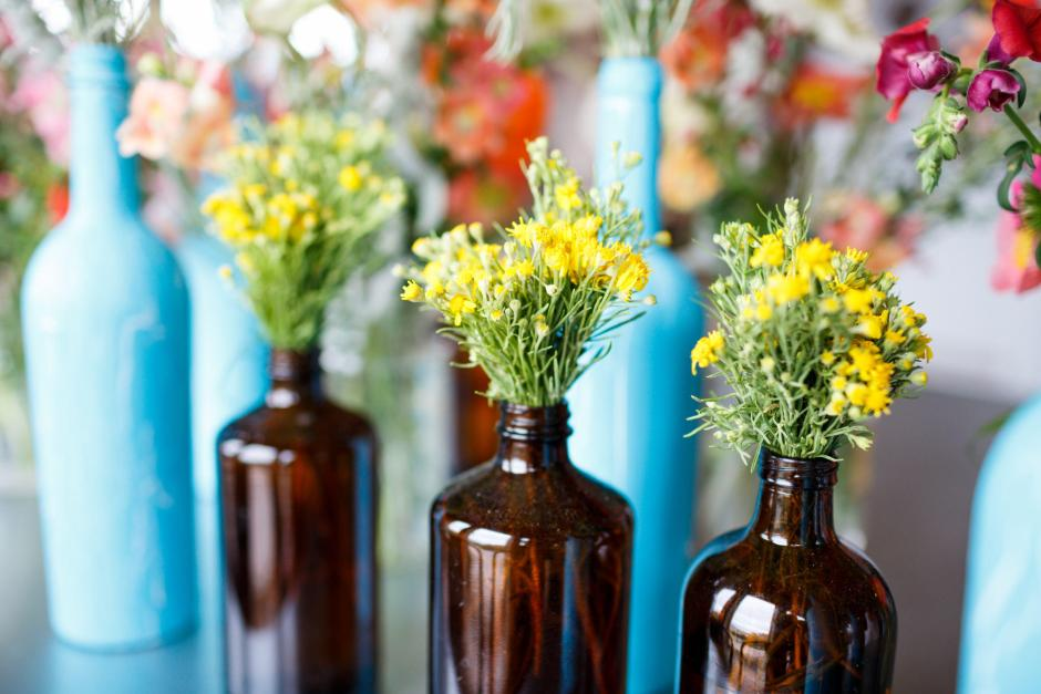 Simple DIY table center peices made with local flowers and old bottles.