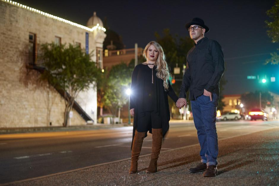 Couple standing in front of blurred traffic at night in downtown Georgetown Halloween engagement