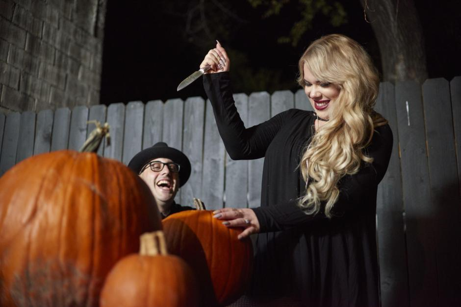Downtown Georgetown Halloween Engagement Photos with Couple Carving Jack-o-lanterns.