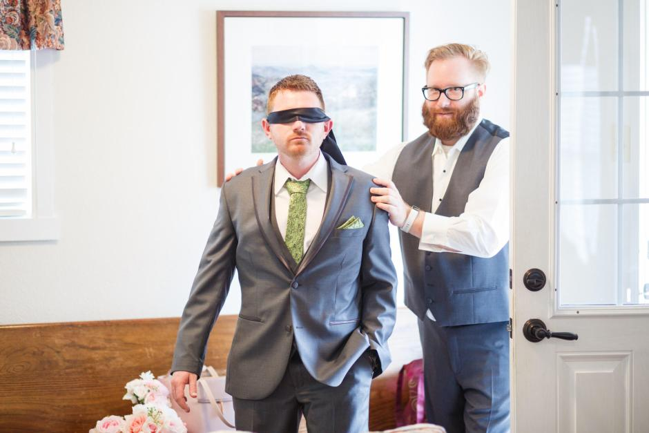 Joshua and Brittany Wedding - Groom being led to the bride blind folded before their wedding ceremony at Hyde Park Presbyterian Church in Austin, TX.