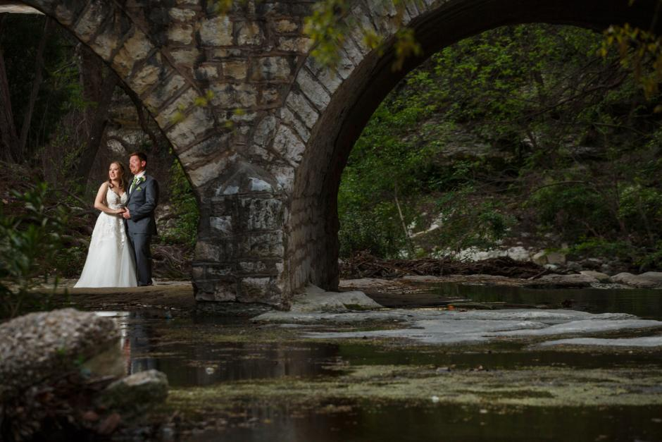 Joshua and Brittany Wedding - Bride and groom portraits under the stone bridge on Waller Creek at the UT Alumni Center wedding reception. Etter-Harbin Alumni Center.