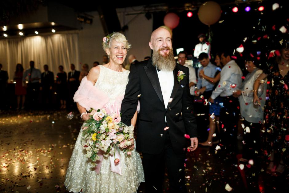 Mike and Kathie exit their Palm Door on Sixth Wedding reception with thrown flower petals.