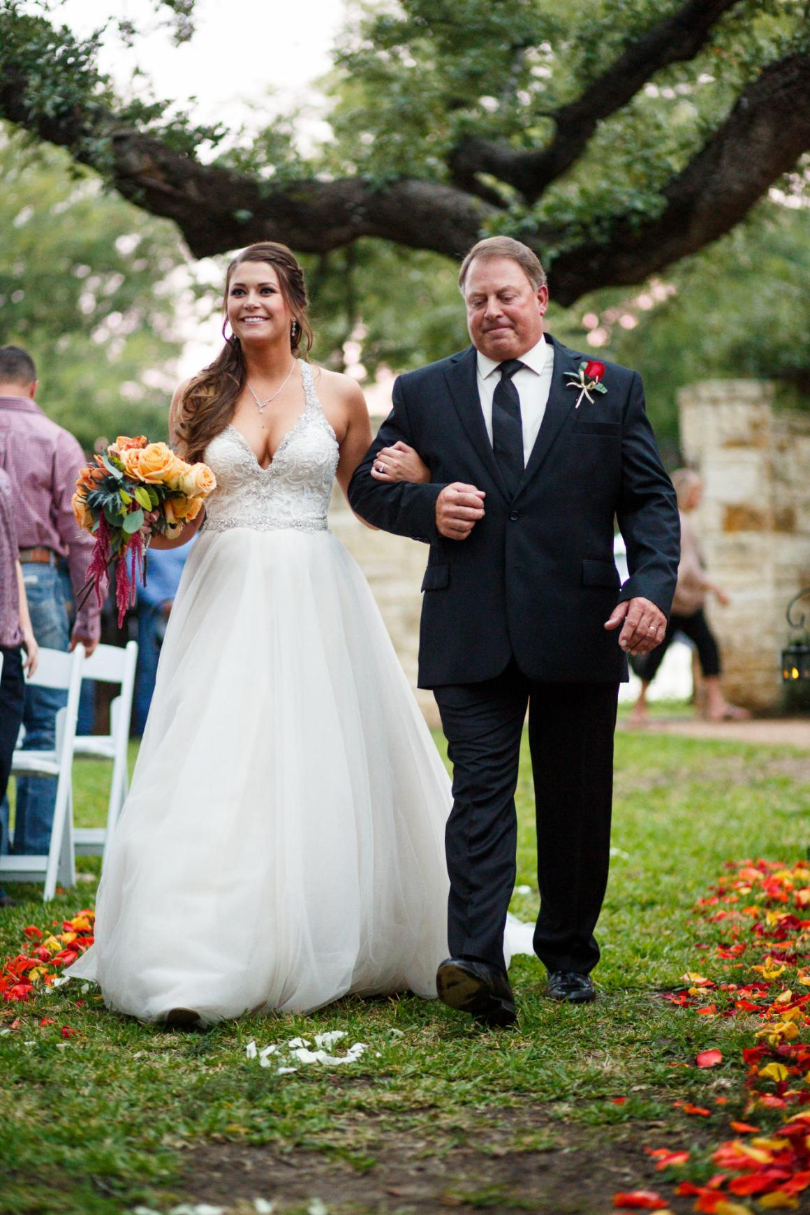 Bride walks down the isle under the spectacular oak trees at a Cathedral Oaks Wedding in Belton, Tx