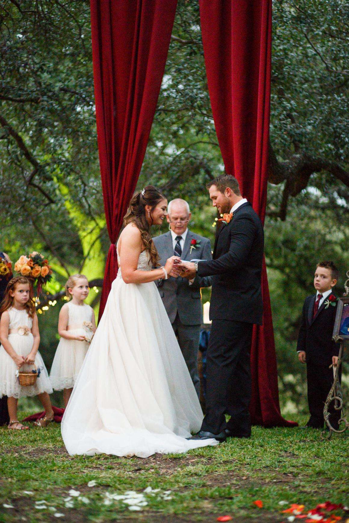 Bride puts the wedding ring on the groom at a Cathedral Oaks Wedding in Belton, Tx