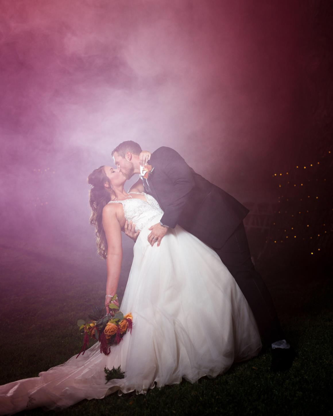 Bride and groom share a kiss on a foggy night at Cathedral Oaks wedding venue in Belton, Tx.