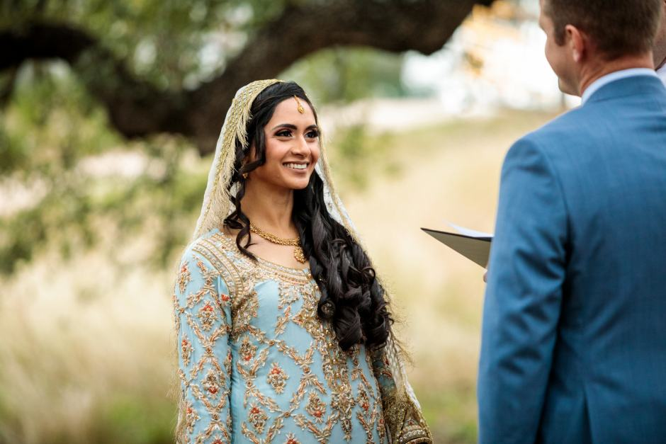 Bride smiles at the groom during her Heart of Texas Ranch wedding in Marble Falls Texas - Indian-Christian Fusion Wedding