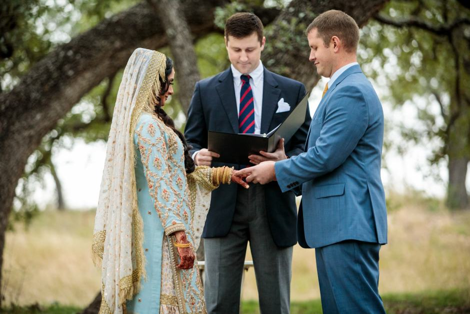 Groom places the wedding ring on the bride's finger during their Heart of Texas Ranch wedding in Marble Falls Texas - Indian-Christian Fusion Wedding