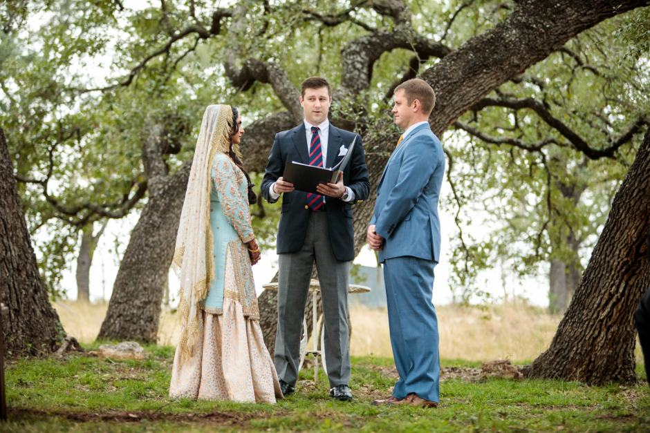 Bride and groom stands together during their wedding under large oak trees at Heart of Texas Ranch in Marble Falls Texas - Indian-Christian Fusion Wedding