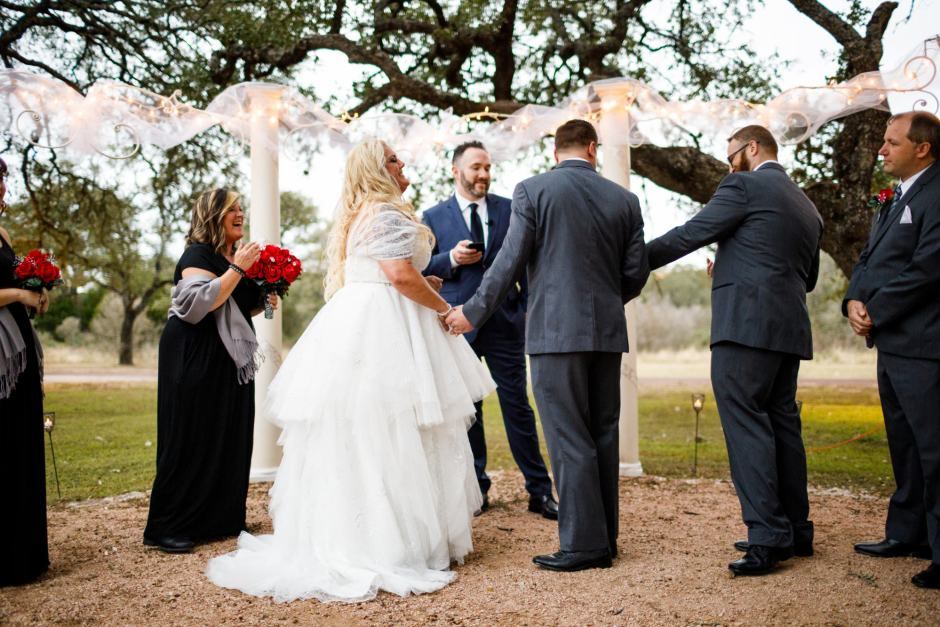 Groom reaches for the ring during their wedding ceremony at Ruby Ranch and Lodge in Buda, Texas.