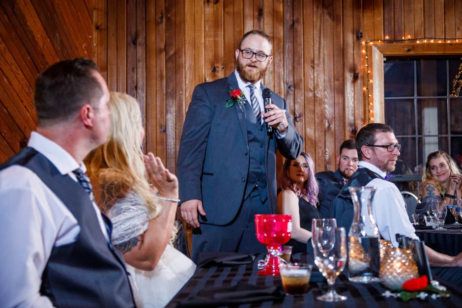 A groomsman toasts the couple during their Buda wedding reception at Ruby Ranch and Lodge.