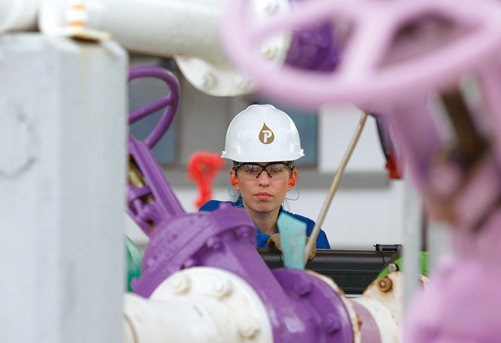 A Petrofac engineer working, surrounded by pipes.