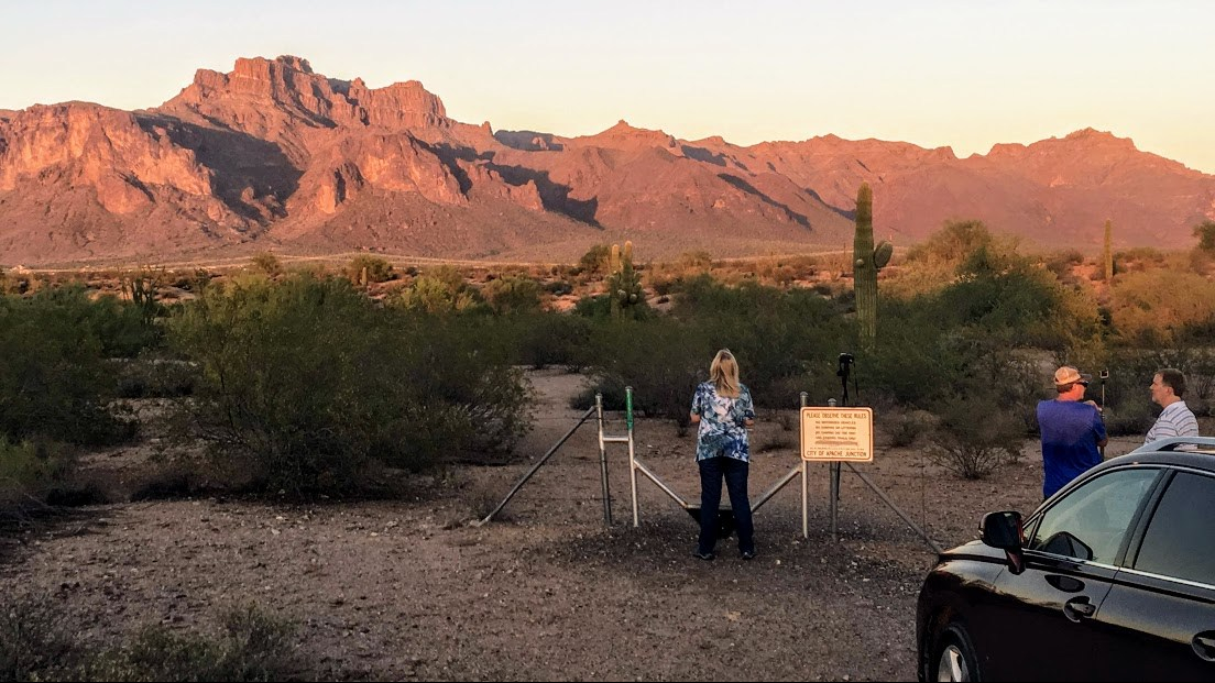 Image of cougar shadow on mountain in background with people in foreground