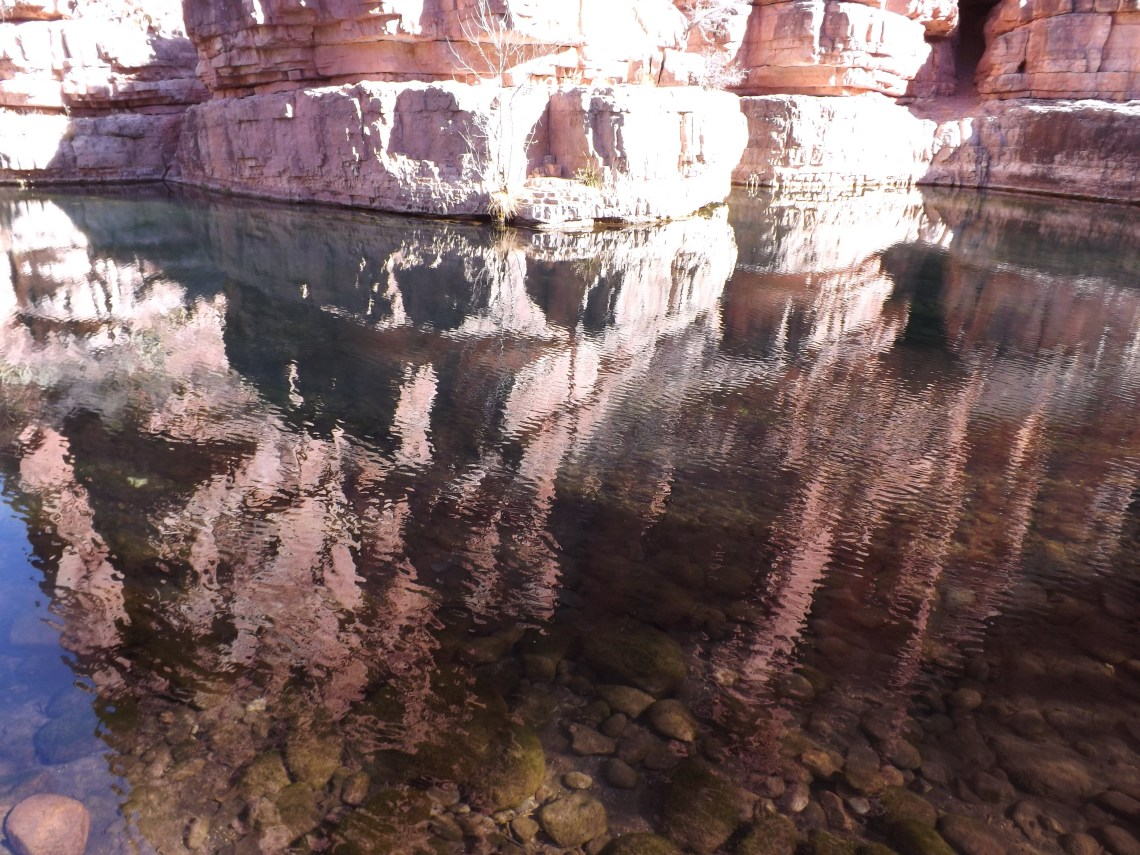 shimmering natural pool with reflection of high canyon wall at the back