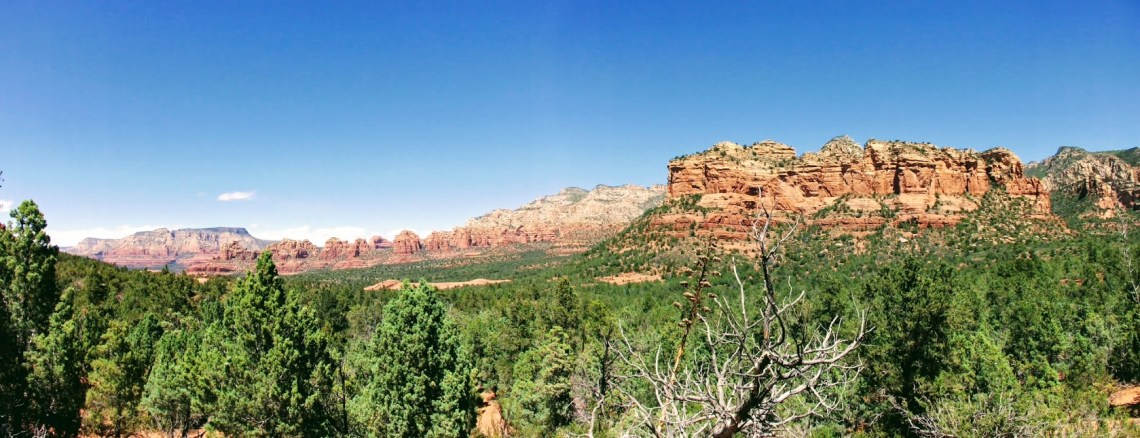 panorama of towering red rock formations with evergreen trees in the foreground