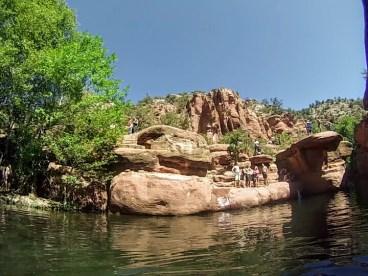 People on rock ledge near creek