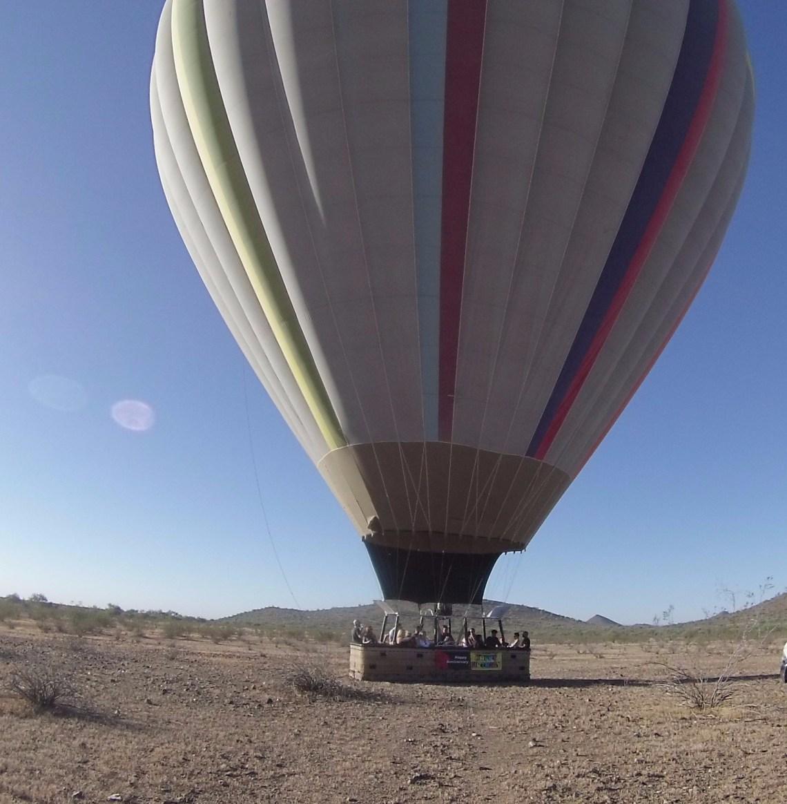 Hot air balloon resting on mostly barren desert