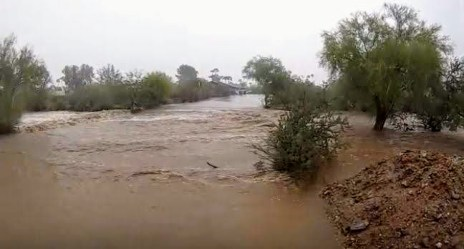 Storm water rushes across a road