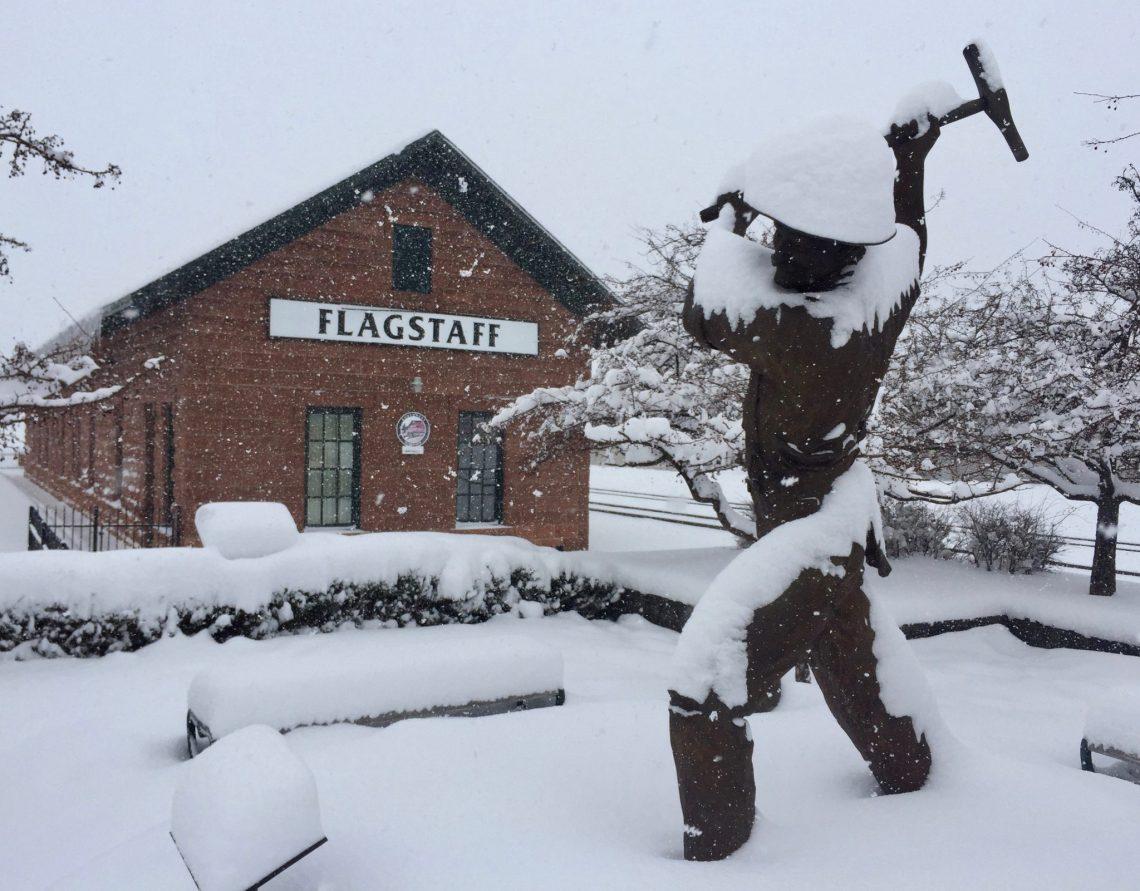 snow on and around bronze statue in Flagstaff, AZ