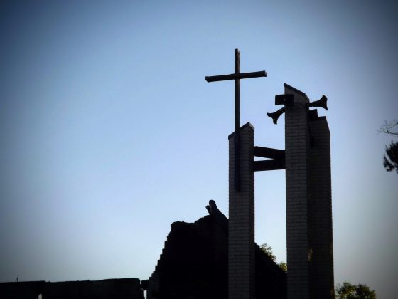 Silhouette of cross standing high above burned down church