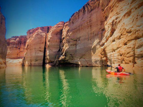 Man in kayak paddling through calm water in a canyon