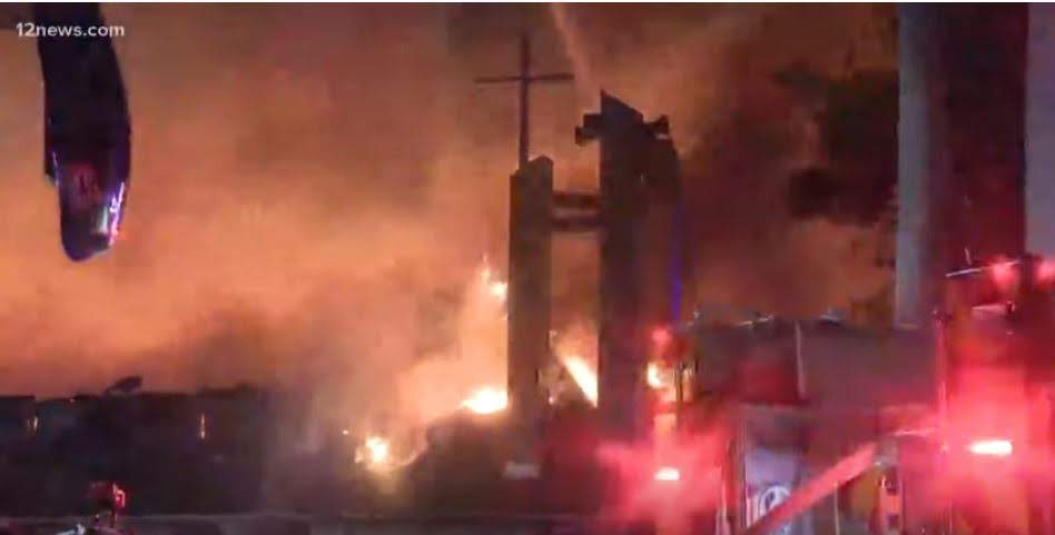 silhouette of cross amid church on fire