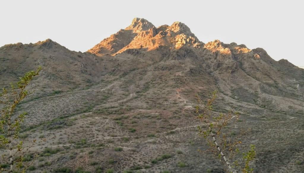 Mountain peak rises above desert landscape is lit up by the sun.
