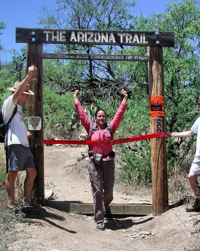 Sirena Rana Dufault passing under the Arizona Trail sign with arms raised high