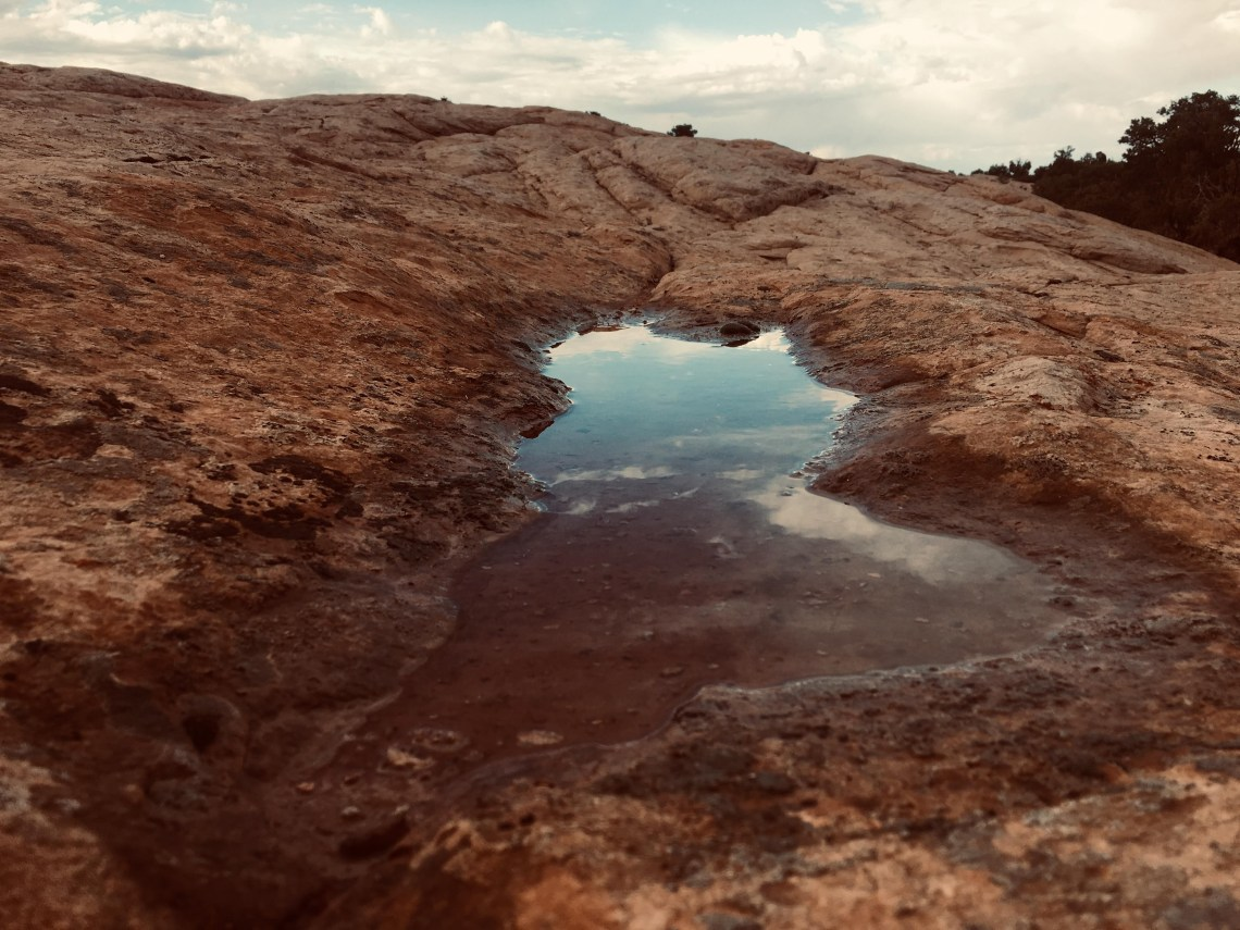 Water puddle in rock creates illusion of an arch