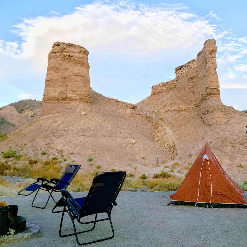 tent and camp chairs with rock spires in background