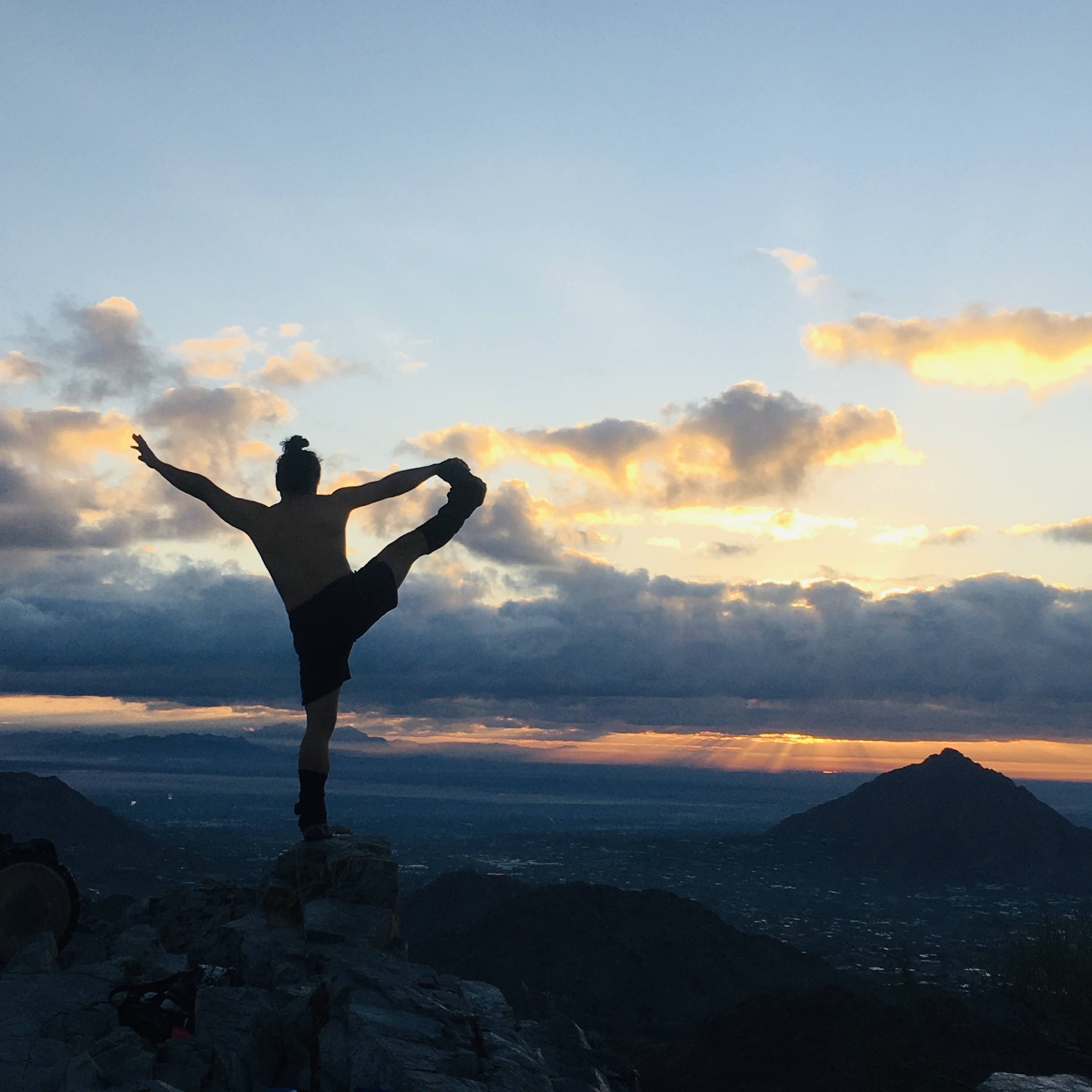 man holding yoga pose on mountaintop