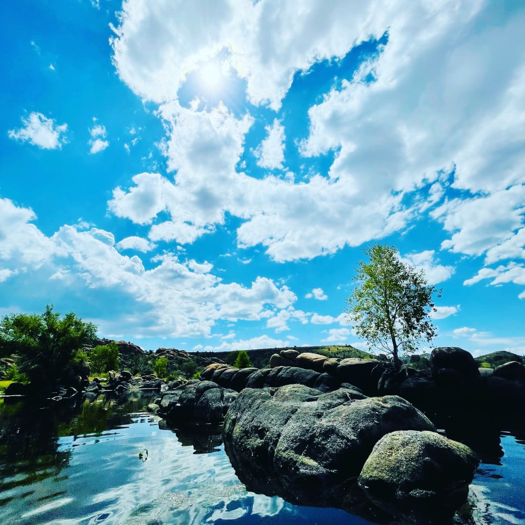 Clouds, granite boulders and the water's reflection