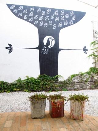Macetas con latones y dibujo en la pared en Amoreira, tienda de diseño en Sao Paulo