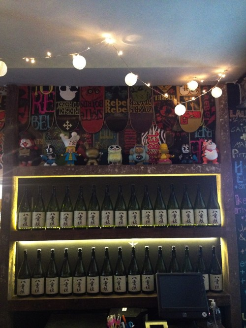 Botellas de sake, figuras y skates en la barra de Fukuro. Foto