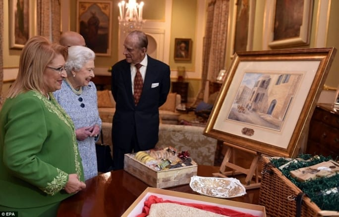 Malta President Marie-Louise Coleiro Preca presenting a painting to the Royals showing the villa where they lived in 1949.