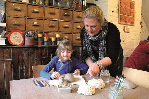 Coalport China Museum workshop, Sara Robinson helps a young visitor
