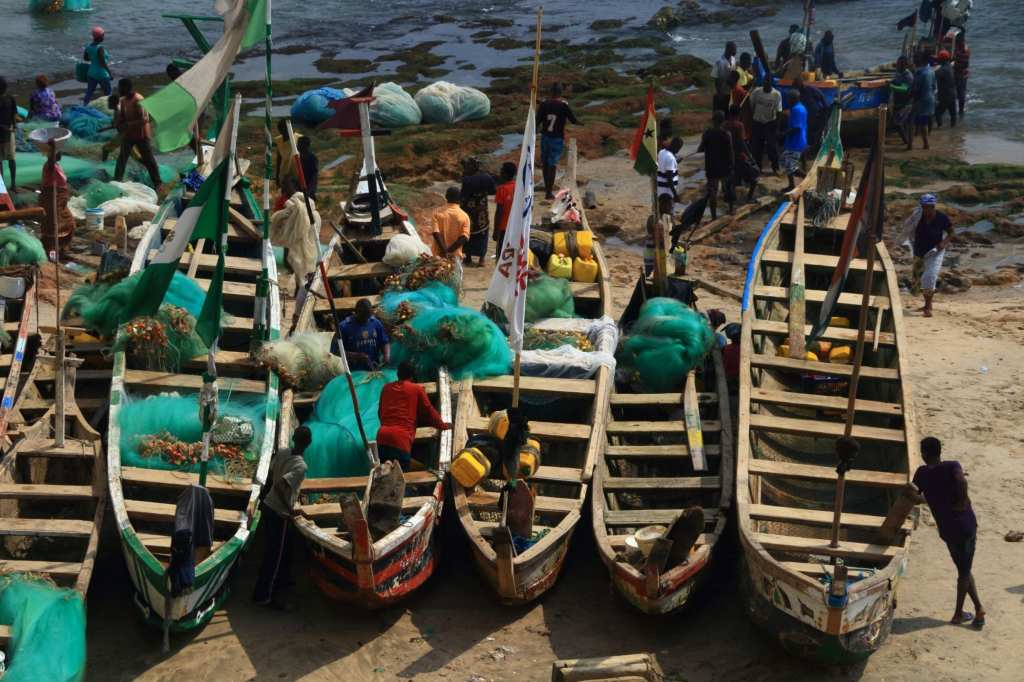 Fishermen around their boats at low tide Just beside Cape Castle