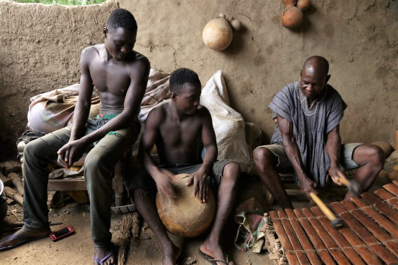 Playing a kalabash drum and the Xylophone Lawra
