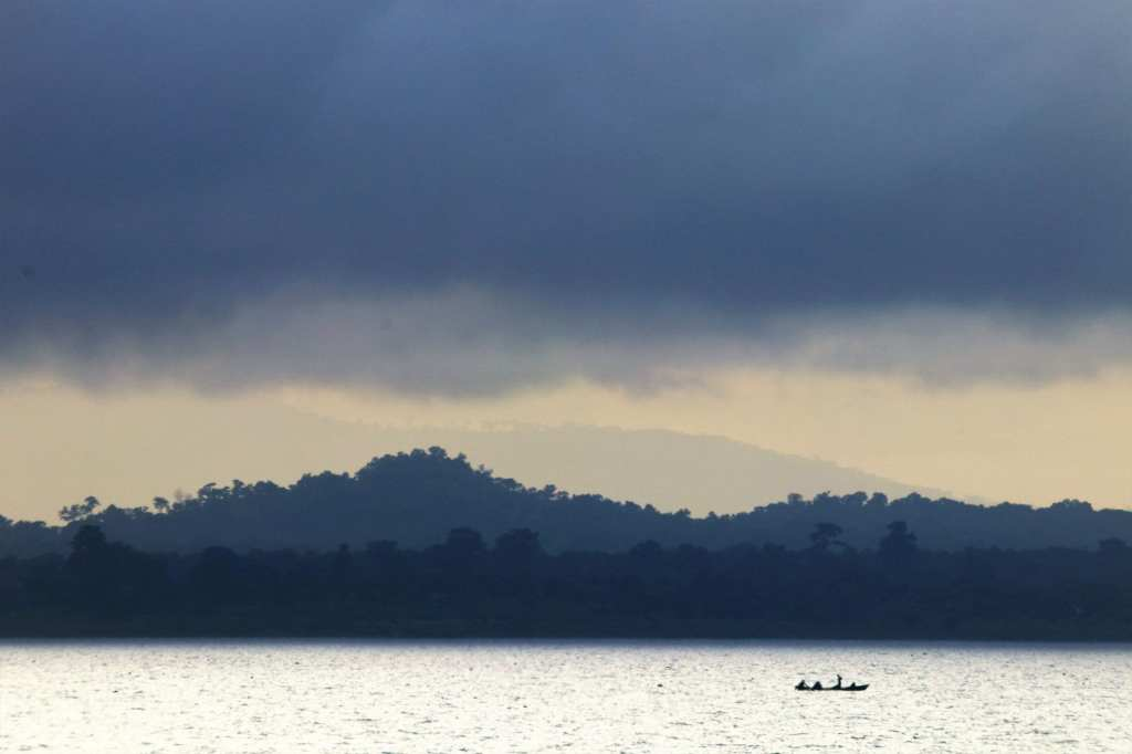 Small wooden fishing boat against a passing storm