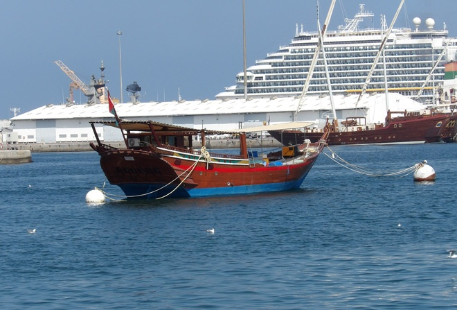 Traditional dhow and big cruise ship in Muscat harbour